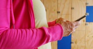 Mujer mayor que usa el teléfono móvil en el vestuario 4k del gimnasio metrajes