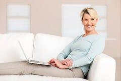 Mujer mayor que usa la computadora portátil imagenes de archivo