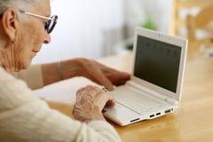 Mujer mayor que usa la computadora portátil fotografía de archivo libre de regalías