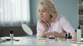 Mujer mayor que usa la porción de cambios de piel relativos a la edad de ocultación del maquillaje costoso almacen de video