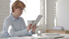 Mujer mayor que usa la tableta en el lugar de trabajo metrajes