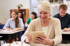 Mujer mayor que usa la tableta en la clase de la enseñanza para adultos Fotos de archivo