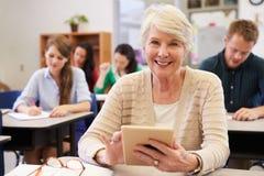 Mujer mayor que usa la tableta en la clase de la enseñanza para adultos Foto de archivo libre de regalías