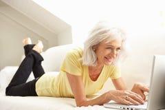 Mujer mayor que usa sentarse de relajación de la computadora portátil en el sofá foto de archivo libre de regalías
