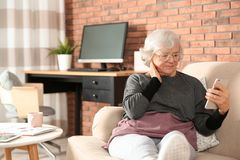 Mujer mayor que usa smartphone en el sofá imagen de archivo libre de regalías