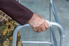 Mujer mayor que usa a un caminante imagenes de archivo