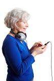 Mujer mayor que usa a un jugador mp3 imágenes de archivo libres de regalías