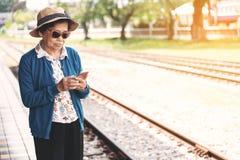 Mujer mayor que usa un teléfono móvil mientras que se sienta en banco en trai fotos de archivo