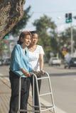 Mujer mayor que usa una calle de la cruz del caminante Imagen de archivo