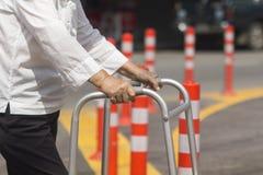 Mujer mayor que usa una calle de la cruz del caminante Fotos de archivo libres de regalías