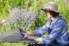 Mujer mayor que usa una tableta digital en su jardín Fotografía de archivo libre de regalías