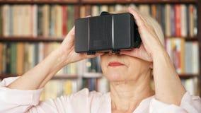 Mujer mayor que usa VR 360 vidrios en casa Personas mayores modernas activas Estantes en fondo almacen de metraje de vídeo