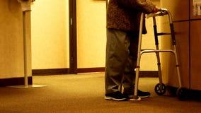 Mujer mayor que usa vueltas y paseos de un caminante hacia la cámara almacen de video