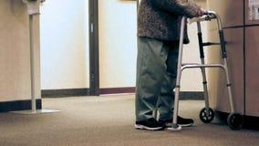 Mujer mayor que usa vueltas y paseos de un caminante hacia la c?mara almacen de metraje de vídeo