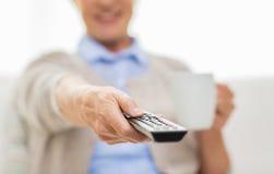 Mujer mayor que ve la TV y que bebe té en casa Fotografía de archivo libre de regalías