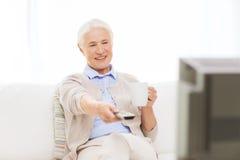 Mujer mayor que ve la TV y que bebe té en casa Imagen de archivo libre de regalías