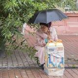 Mujer mayor que vende el artware en la lluvia en Nizhny Novgorod, Federación Rusa Foto de archivo