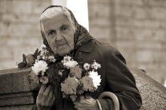 Mujer mayor que vende las flores Imagen de archivo libre de regalías