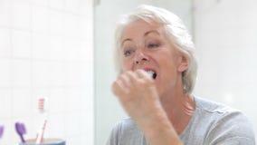 Mujer mayor reflejada en dientes de cepillado del espejo del cuarto de baño almacen de video