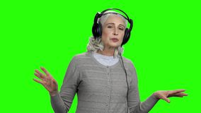 Mujer mayor relajada en auriculares en la pantalla verde metrajes