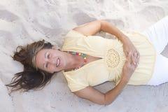Mujer mayor relajada feliz que miente en arena fotografía de archivo libre de regalías