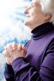 Mujer mayor religiosa cristiana que ruega Fotos de archivo