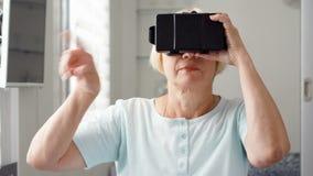 Mujer mayor rubia en blanco usando VR 360 vidrios en casa Haciendo hojee, enfoque y golpee ligeramente los gestos almacen de video