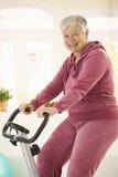 Mujer mayor sana en la bici de ejercicio Imagenes de archivo