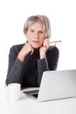 Mujer mayor seria con su ordenador portátil fotografía de archivo