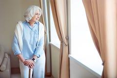 Mujer mayor sola con la muleta fotos de archivo libres de regalías