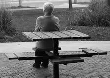 Mujer mayor sola en banco imagenes de archivo