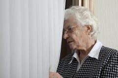 Mujer mayor sola que mira fuera de ventana Imagenes de archivo