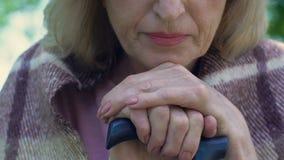Mujer mayor sola que se inclina en el bastón y que piensa en la vida, retiro almacen de metraje de vídeo