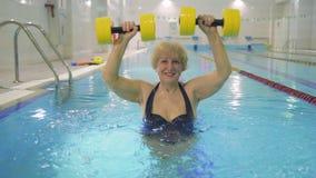 Mujer mayor sonriente atractiva con pesas de gimnasia en piscina metrajes
