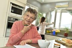 Mujer mayor sonriente con el cuidador casero en el fondo fotos de archivo libres de regalías