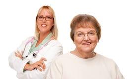 Mujer mayor sonriente con el doctor Behind foto de archivo