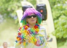 Mujer mayor sonriente con la peluca colorida y un nec colorido de la flor Foto de archivo