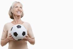 Mujer mayor sonriente en balón de fútbol que se sostiene casual contra el fondo blanco fotografía de archivo libre de regalías