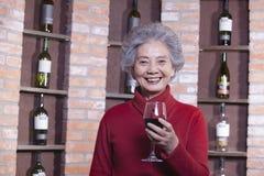 Mujer mayor sonriente en el suéter rojo que sostiene el vidrio de vino, retrato Fotos de archivo