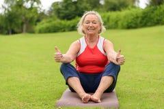 Mujer mayor sonriente en la estera de la yoga con los pulgares para arriba Imagenes de archivo