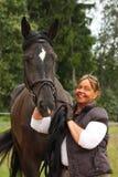 Mujer mayor sonriente feliz y retrato negro del caballo Foto de archivo libre de regalías