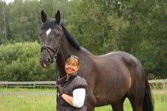 Mujer mayor sonriente feliz y retrato negro del caballo Imagenes de archivo