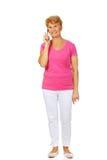Mujer mayor sonriente que habla a través del teléfono Fotografía de archivo