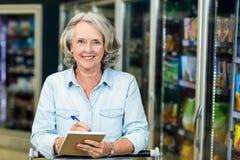 Mujer mayor sonriente que lleva a cabo la lista fotos de archivo