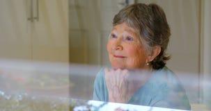 Mujer mayor sonriente que mira a través de la ventana 4k almacen de video