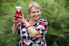 Mujer mayor sonriente que muestra el jarro con la fruta guisada fresca Foto de archivo