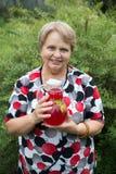 Mujer mayor sonriente que muestra el jarro con la fruta guisada fresca Imágenes de archivo libres de regalías
