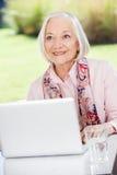 Mujer mayor sonriente que parece ausente mientras que usa Foto de archivo