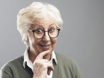 Mujer mayor sonriente que piensa con la mano en la barbilla imagen de archivo