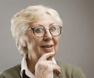 Mujer mayor sonriente que piensa con la mano en la barbilla fotografía de archivo libre de regalías